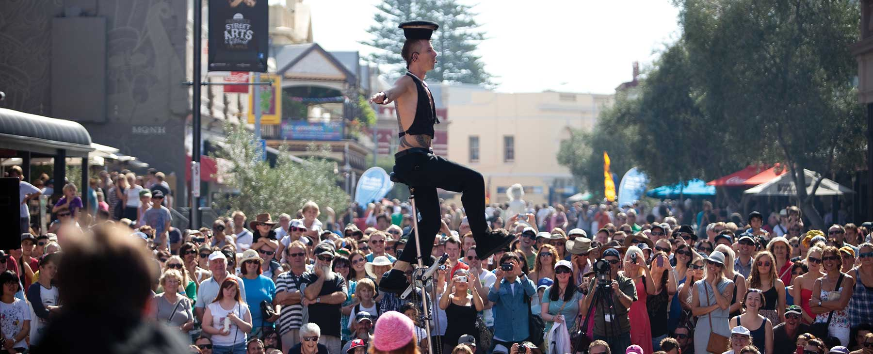 Acrobat balancing on a unicycle in front of a large crowd