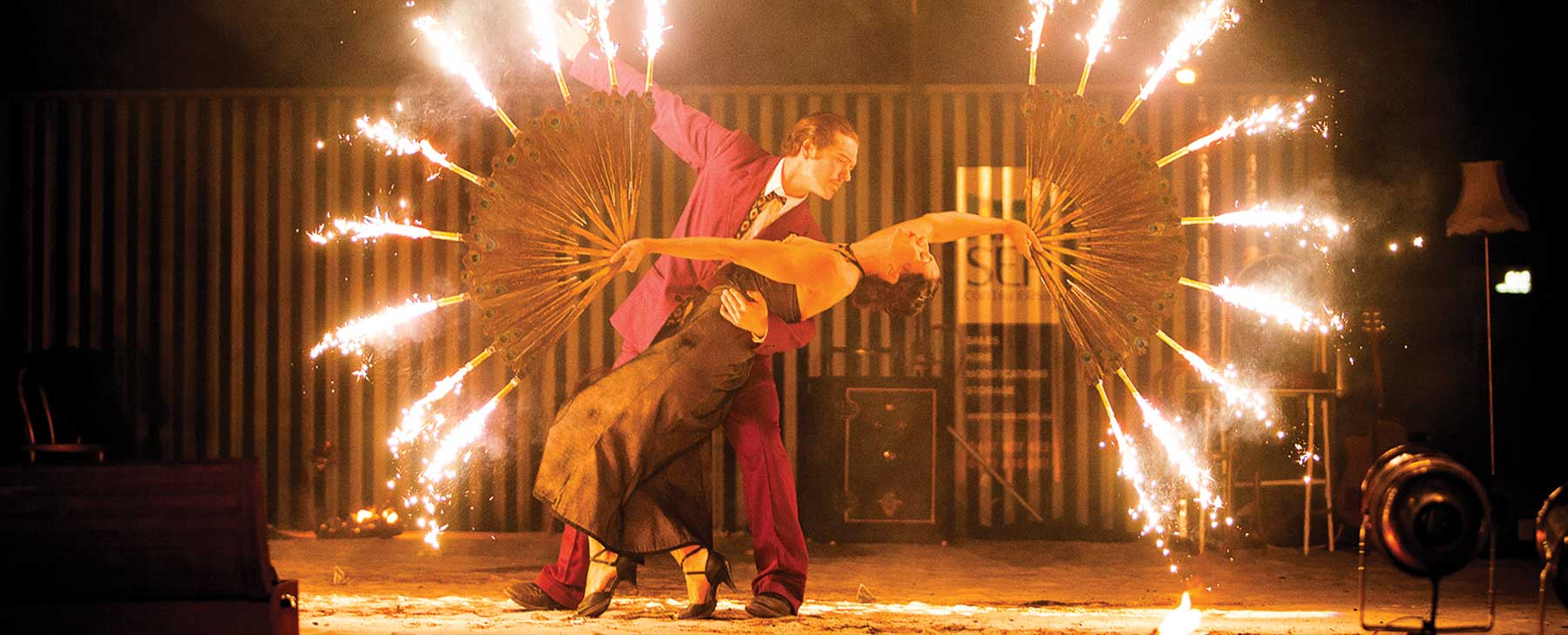 Spanish dancers juggle with fire in front of shipping container